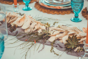 table with seashells as a table runner and turquoise glassware