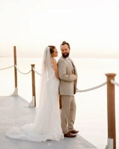 bride in white dress and groom in tan suit on boardboalk