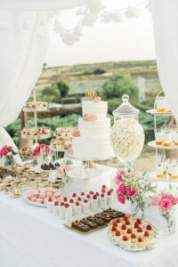dessert table with popcorn, wedding cake, brownies, fruit, pudding, cake pops