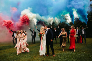 Wedding party walking through grass holding red, white and blue smoke bombs. Festive Americana Wedding Must Haves