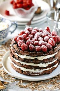 chocolate waffles stacked with cream layered inbetween with fresh raspberries