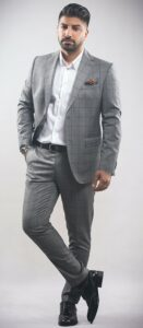 Man in grey plaid suit without a tie, colorful pocket square, black belt and shoes, and silver watch