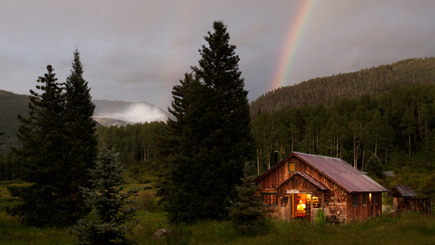 cabin nestled in the woods and hills with the steam from the hot springs rising in the background. A rainbow lights up the sky.