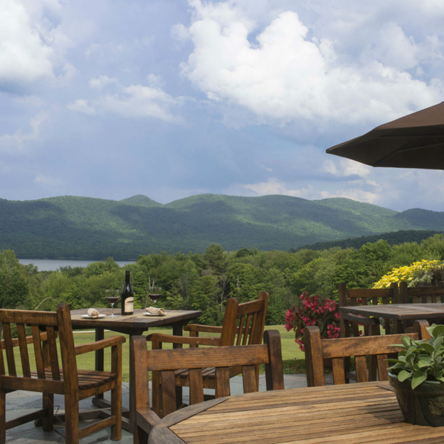 tables and chairs on a deck overlooking the mountain view