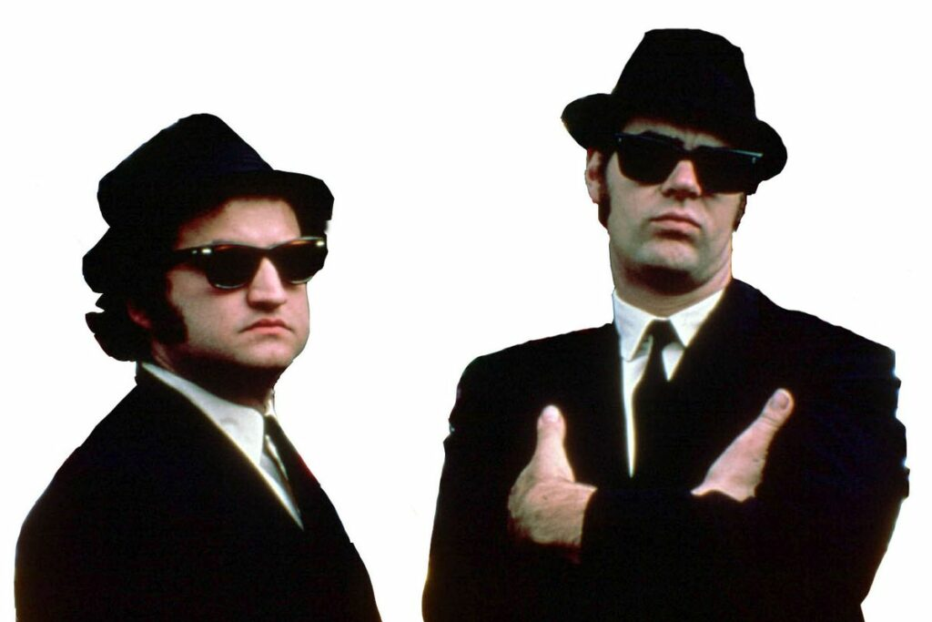blues brothers in black suits, white shirts, black ties, and black fedoras