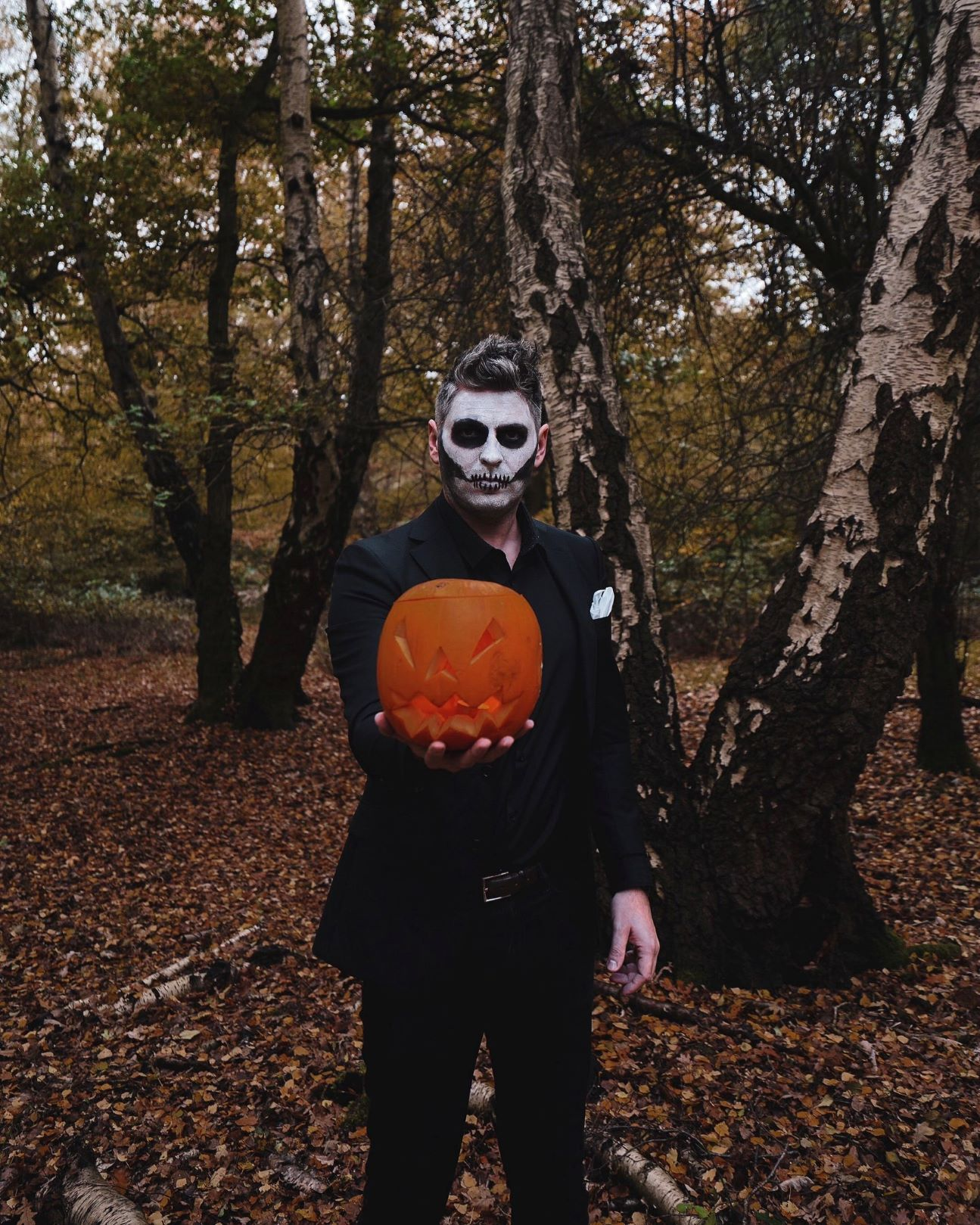 man in woods wearing all black suit with face painted like a skeleton and holding a carved pumpkin