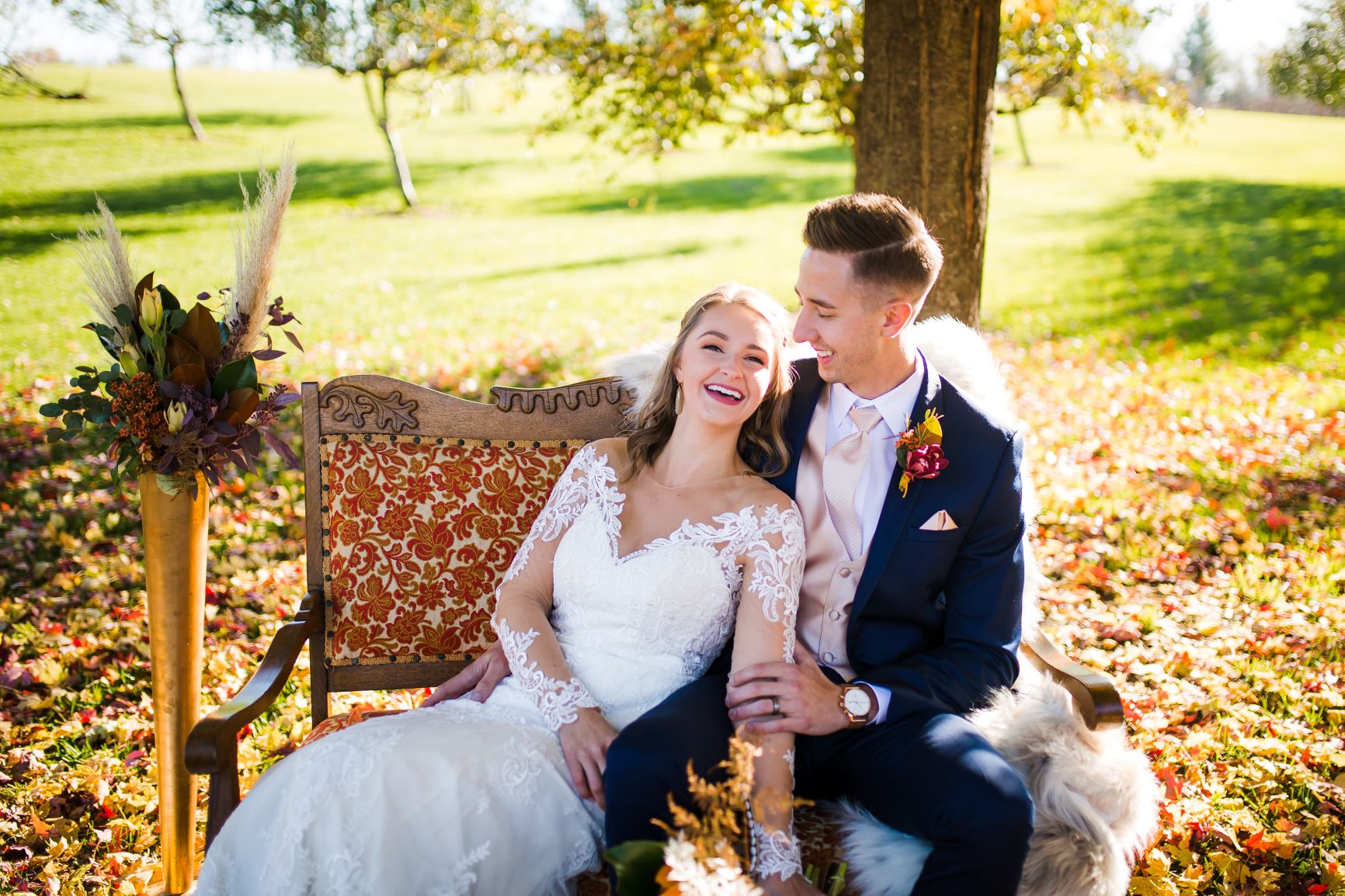 bride and groom sitting on a couch in a grassy area surrounded by fall foliage